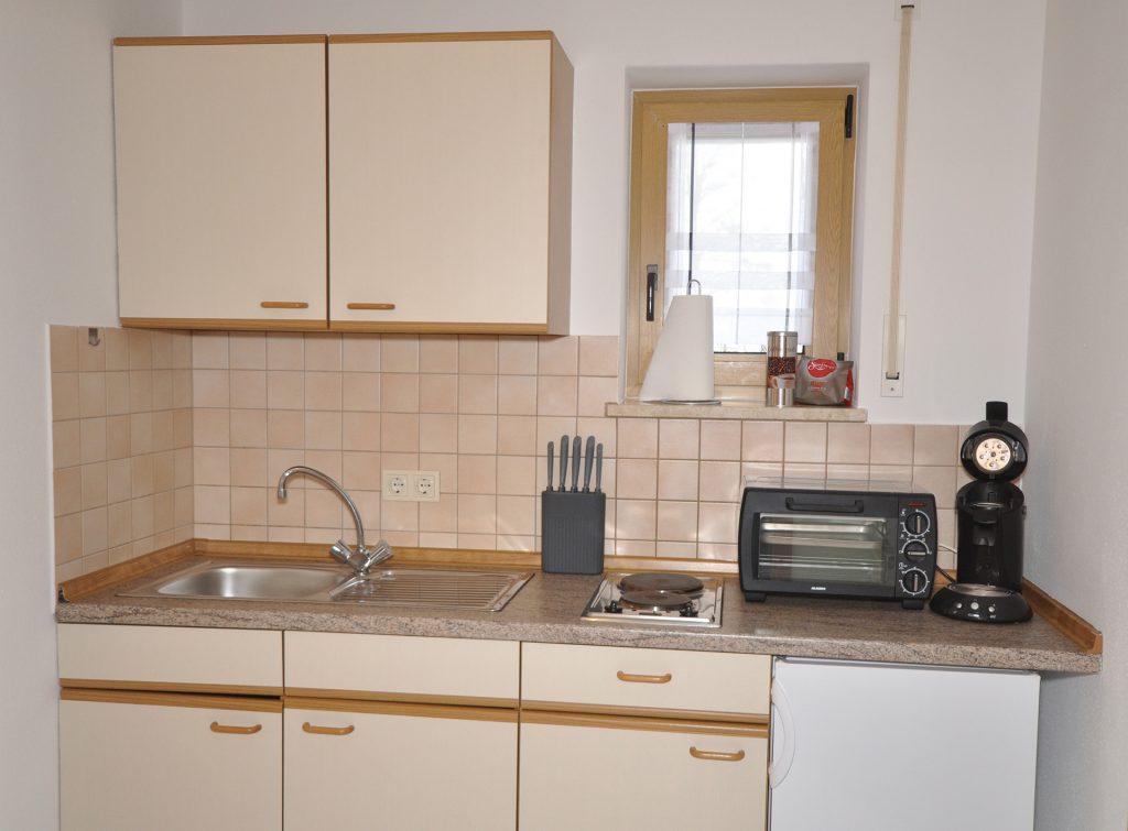 Küchenzeile mit Waschbecken, Herdplatten & kleinem Ofen